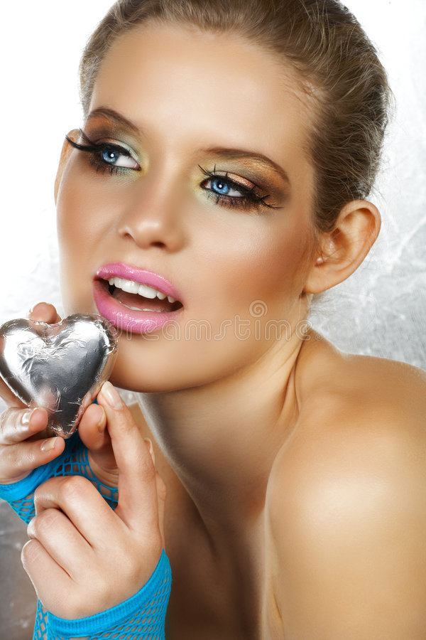 Blond beautiful woman with heart. Blond beautiful woman with blue eyes and fashion make-up holding a silver heart, wearing blue fingerless gloves. Not isolated royalty free stock photography