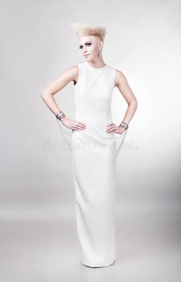 blond beautiful woman in long white dress with creative hairstyle royalty free stock images