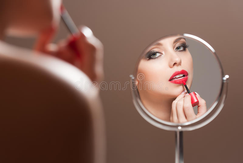 Blond beauty putting on makeup. stock photography