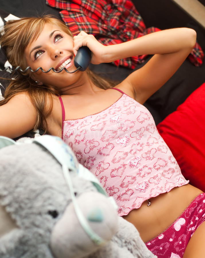 Blond in bed with telephone royalty free stock photography