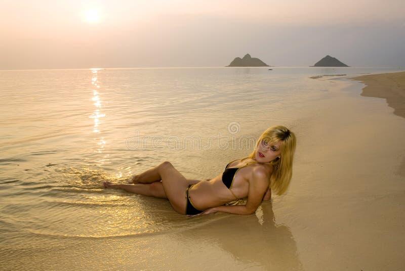 Blond in bikini bij zonsopgang stock foto