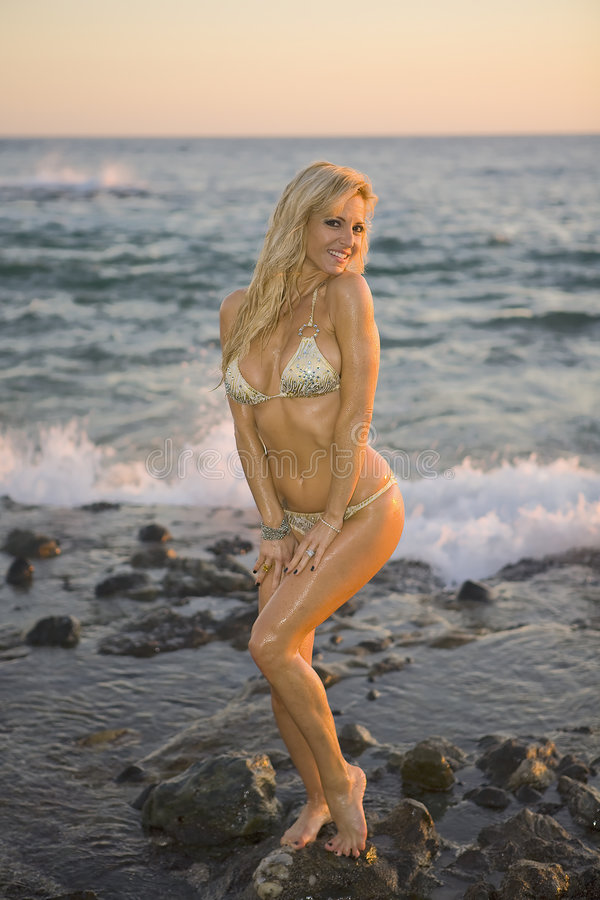 Blond in Bikini smiling on Rocks. Beautiful Blond Woman smiling on Rocks at the Beach stock photos
