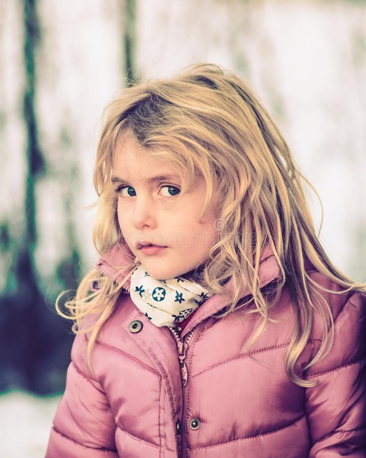 Blond blue eyed little girl dressed up for winter. Blue eyed blond little girl dressed up for winter playful looking at me royalty free stock images