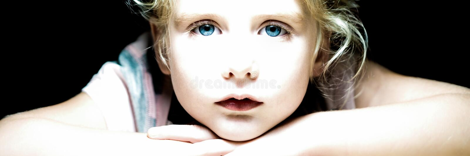 Blond blue eyed little girl looking at me stock images