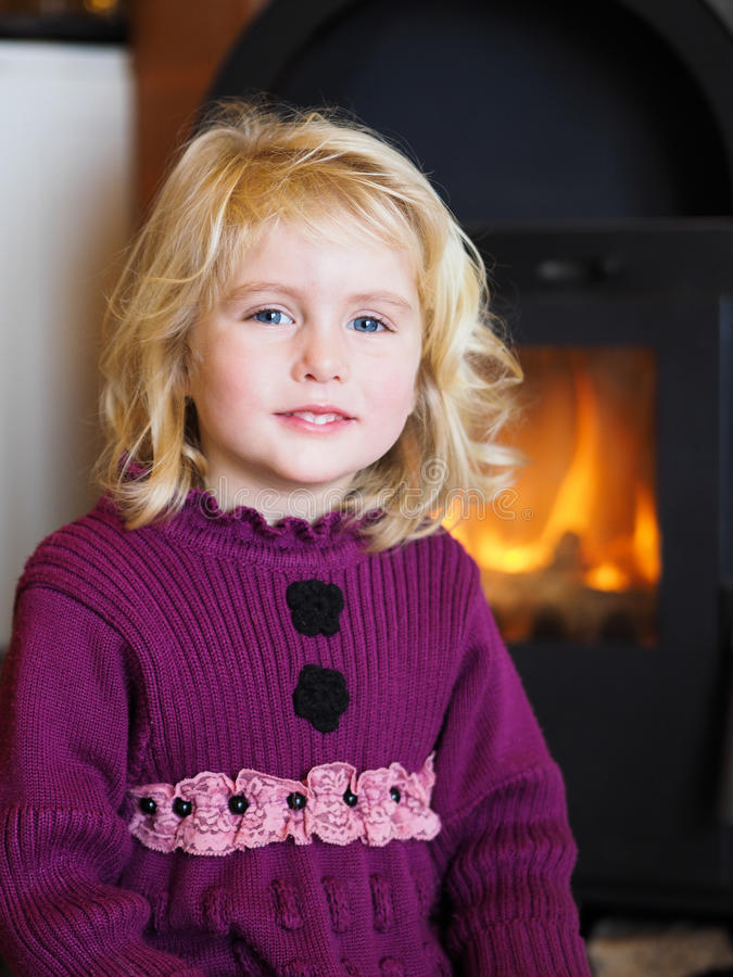 Blond blue eyed little girl sitting in front of a fireplace. Smiling blond blue eyed little girl sitting by a fireplace royalty free stock images