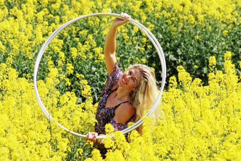 Blond bondaktig flicka i klänning för blom- tryck på rapsfröfältet royaltyfri bild