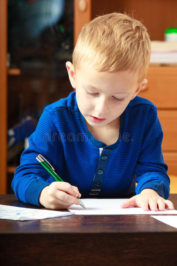 Blond boy child kid with pen writing on piece of paper. At home. Happy childhood. Blond boy child kid with pen writing on piece of paper doing homework. At home royalty free stock images