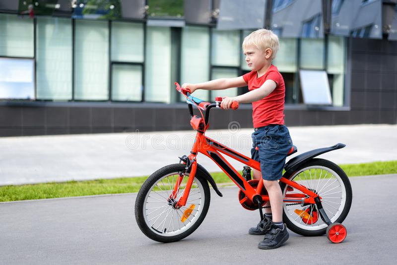 Blond boy on a children`s bicycle. Urban background.  stock photo