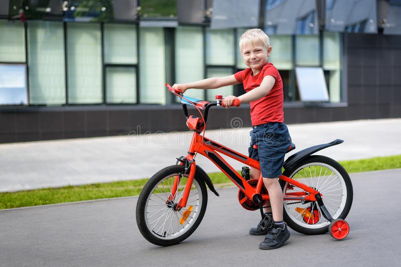 Blond boy on a children`s bicycle. Urban background.  stock photos