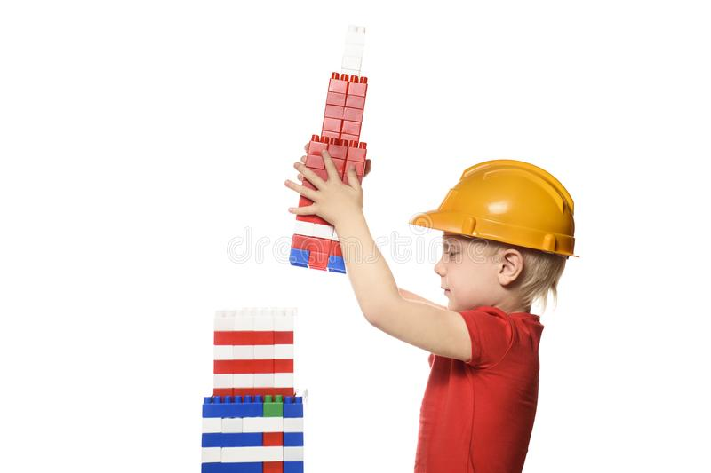 Blond boy in construction helmet and red t-shirt builds a skyscraper from the details of the designer. Isolate on white background stock photos