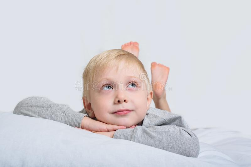 Blond boy lies with his head in his hands and looks up. White background royalty free stock photos