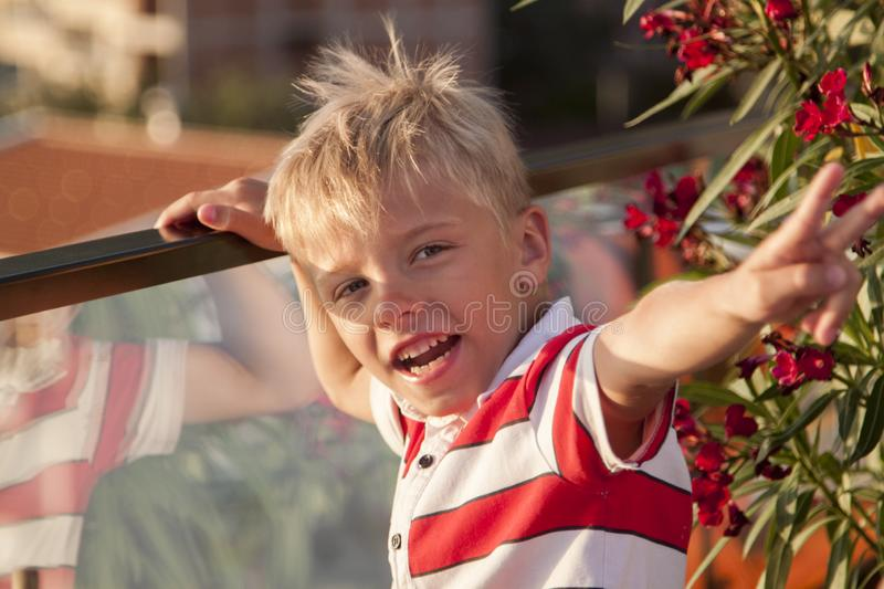 blond boy looks at the camera and throws his hand up with a vict royalty free stock photography