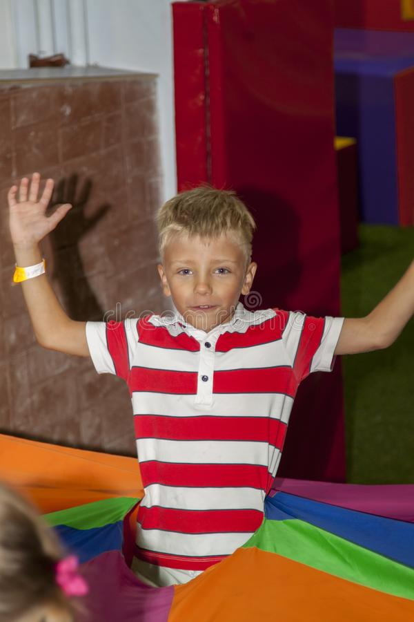 Blond boy play crawling through tube in kids zone in amusement p royalty free stock image