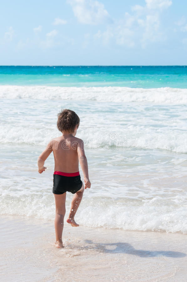 Blond boy runs into the sea. Blond boy runs into the turquoise waters of the Caribbean royalty free stock photos