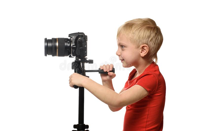 Blond boy shoots video on DSLR camera. Side view. White background, isolate stock photo