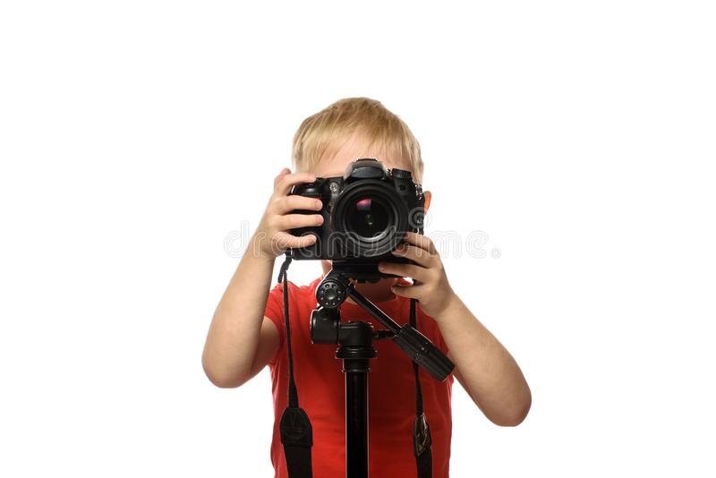 Blond boy takes pictures with a SLR camera. Front view. White background, isolate royalty free stock images
