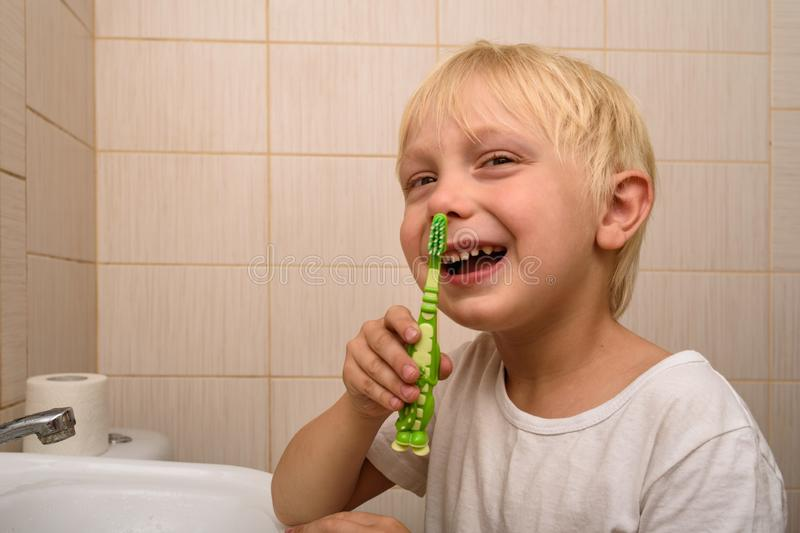 Blond boy with a toothbrush in hand, bathroom. Healthy habits royalty free stock photography