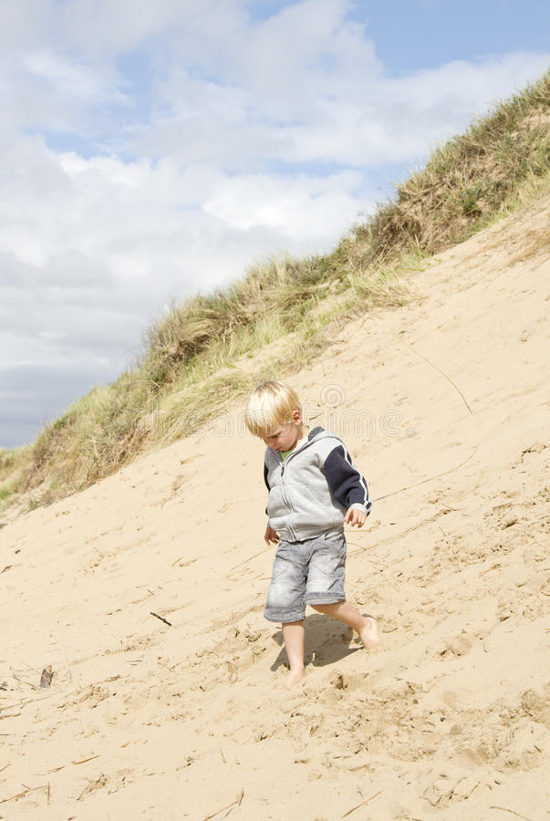 Blond boy walking down sand dune royalty free stock photos