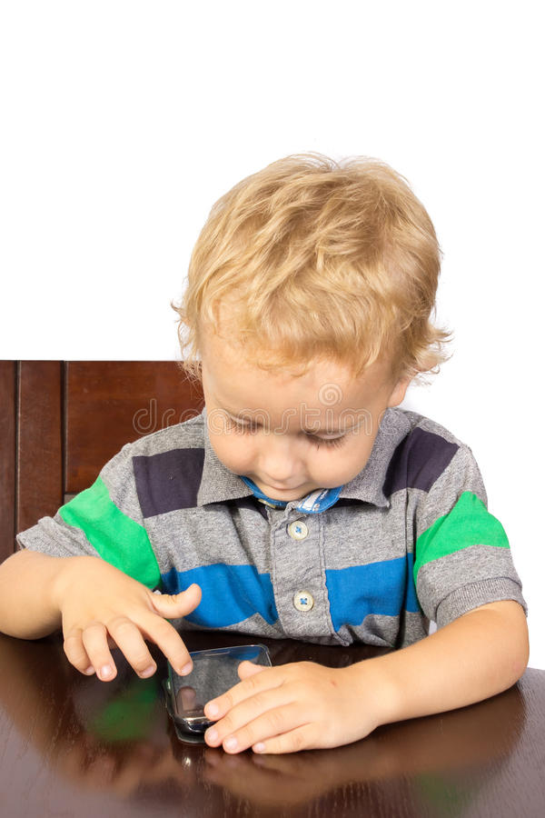 Blond boy wants to call on his cell phone. And dials stock photography