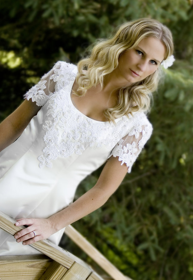 Blond bride in white dress. Three quarter body portrait of young bride with blond hair in traditional white wedding dress, green nature background stock photos