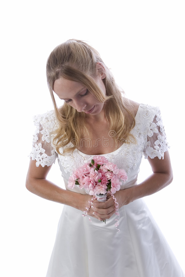 Blond bride in white dress. Thoughtful young bride in white dress holding bouquet and looking downwards; isolated on white background royalty free stock photography