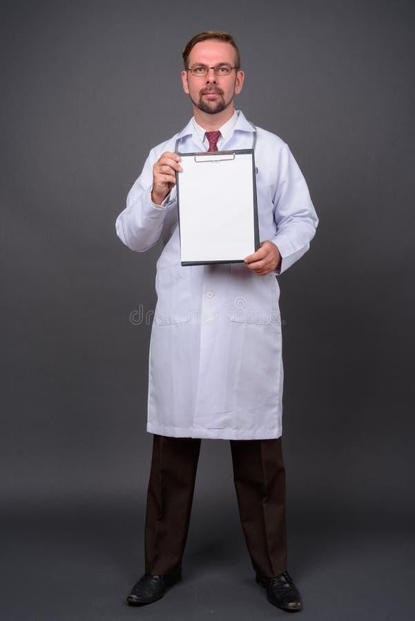 Blond brodata mężczyzna lekarka z goatee przeciw szaremu tłu obrazy royalty free