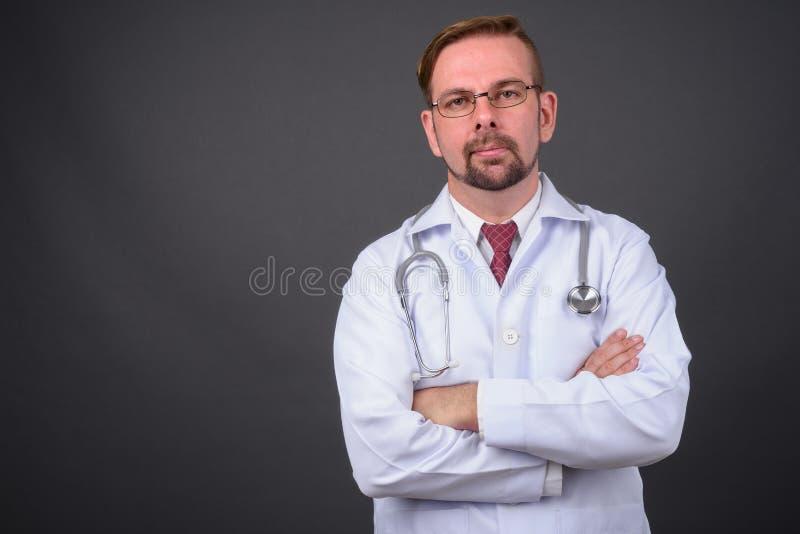 Blond brodata mężczyzna lekarka z goatee przeciw szaremu tłu obrazy stock