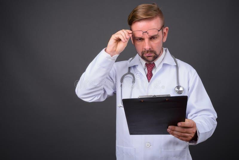 Blond brodata mężczyzna lekarka z goatee przeciw szaremu tłu zdjęcia stock