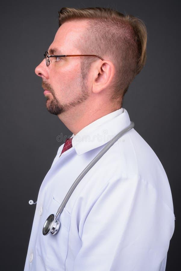 Blond brodata mężczyzna lekarka z goatee przeciw szaremu tłu fotografia royalty free