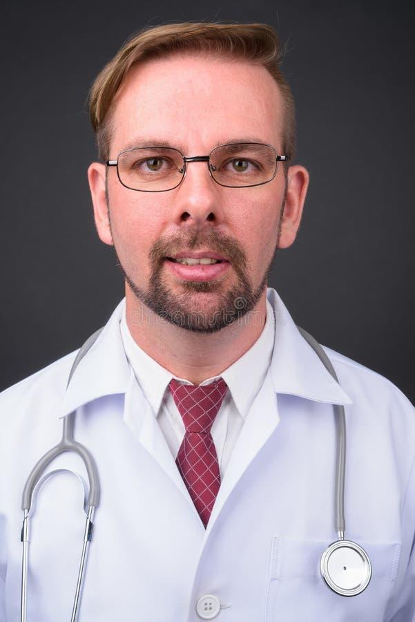 Blond brodata mężczyzna lekarka z goatee przeciw szaremu tłu zdjęcie royalty free