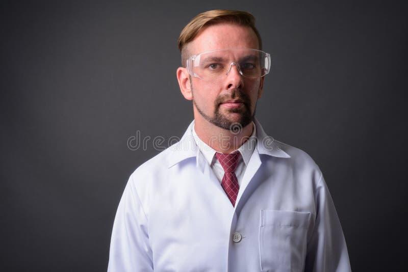 Blond brodata mężczyzna lekarka z goatee przeciw szaremu tłu zdjęcia royalty free
