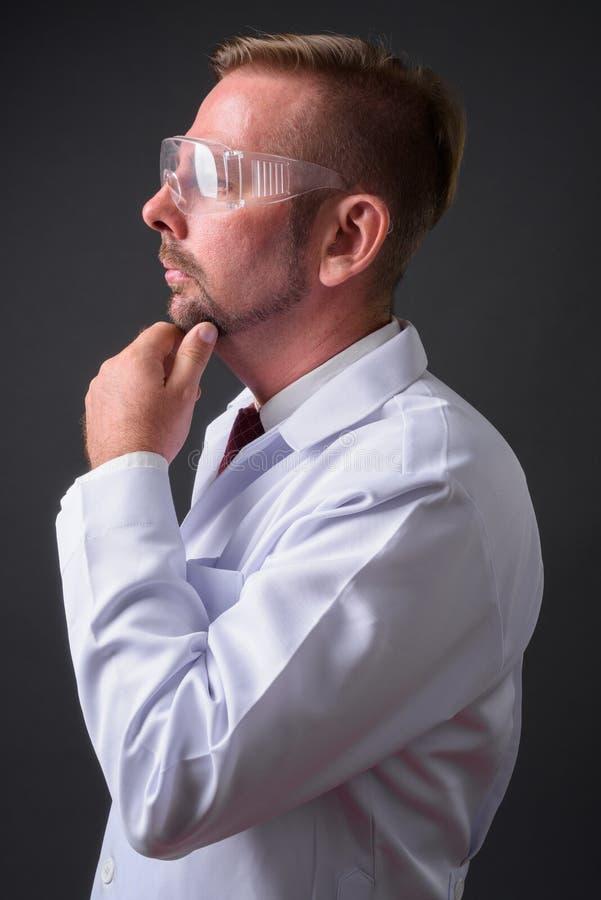 Blond brodata mężczyzna lekarka z goatee przeciw szaremu tłu zdjęcie stock