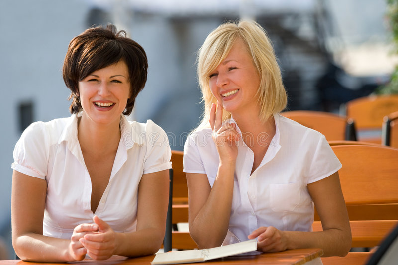 Blond and brunette girls sitting in coffee house royalty free stock image