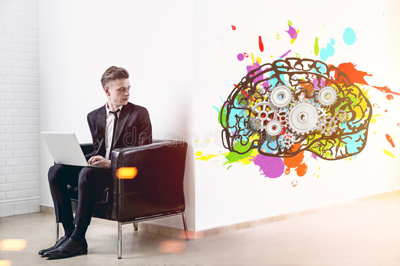 Blond businessman with a laptop, brain, cogs. Young and handsome businessman with a laptop is sitting in an armchair in a white office with a giant colorful royalty free stock photos