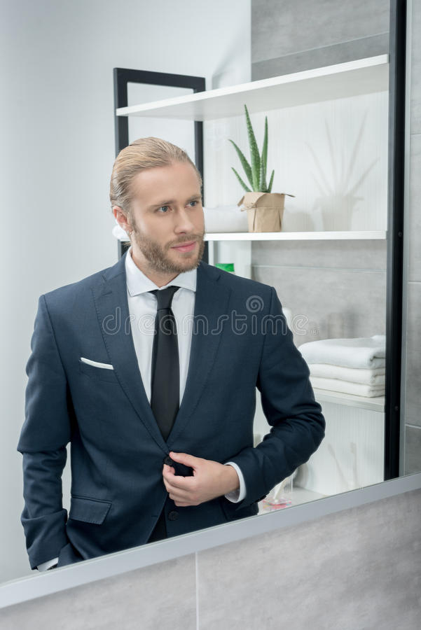 Blond businessman in suit looking in the mirror in bathroom royalty free stock photos