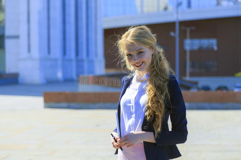 Blond businesswoman standing over big business center building. Blond businesswoman standing over big office business center building. Lady holding pen and stock image