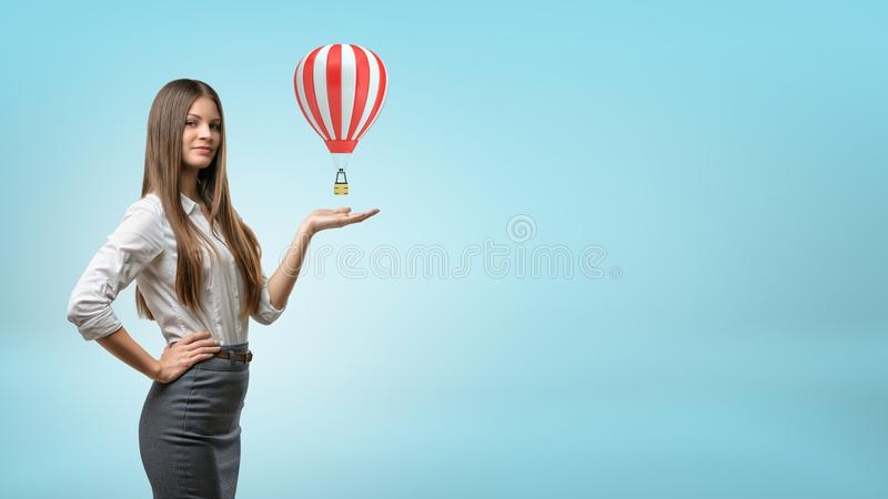 A blond businesswoman stands and holds one hand palm up with small red and white hot air balloon above it. Travel agent. Insurance abroad. Hotel booking stock photo