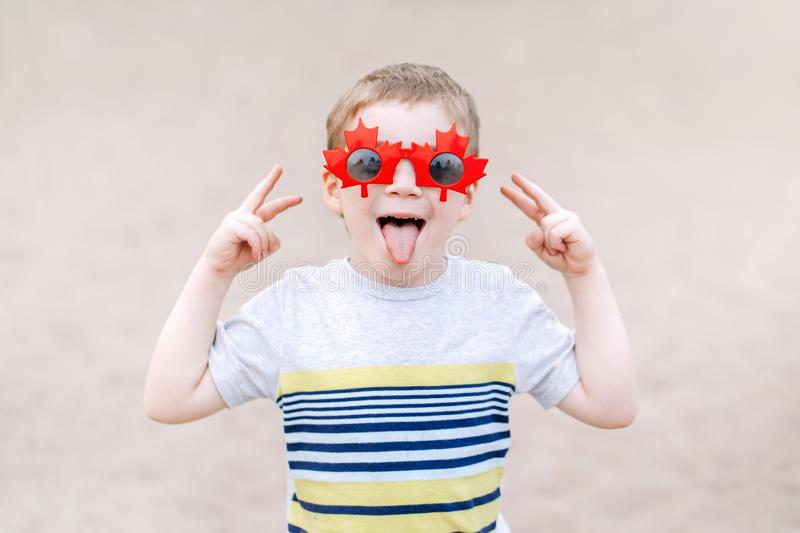 blond Caucasian boy wearing funny Canadian sunglasses with maple leaf. Child kid celebrating Canada Day stock photo