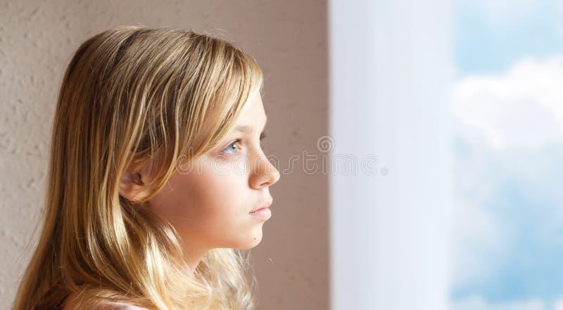 Blond Caucasian flicka nära fönster med blå himmel royaltyfri fotografi