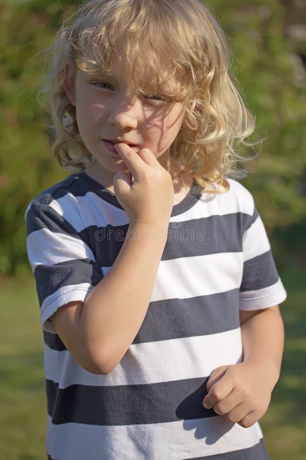 Blond chłopiec gryźć jego gwoździe obraz stock