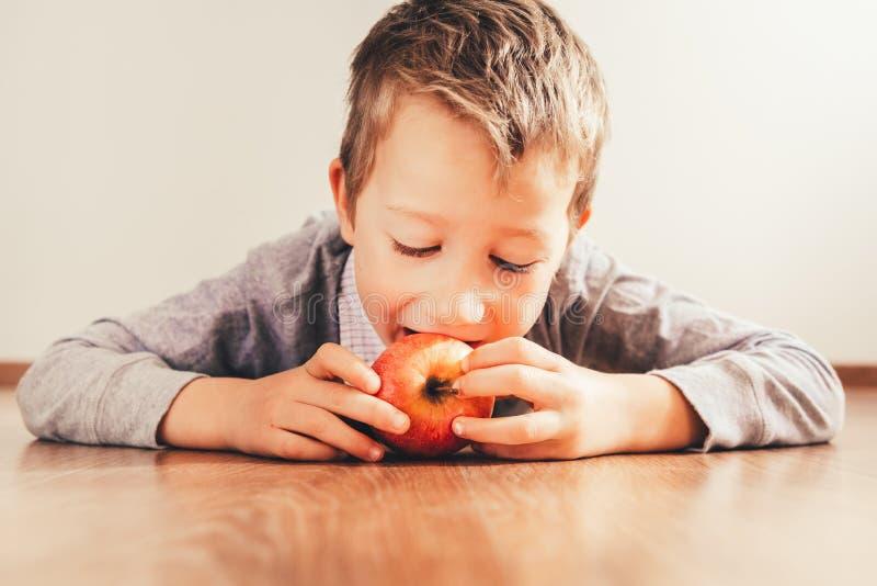 Blond chłopiec leżący na podłodze, zaczepiający jabłko za zdrową przekąskę fotografia stock