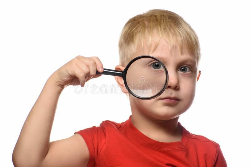 Blond chłopiec z powiększać - szkło w jego ręki odkrywca troch? Bia?y t?o zdjęcie stock