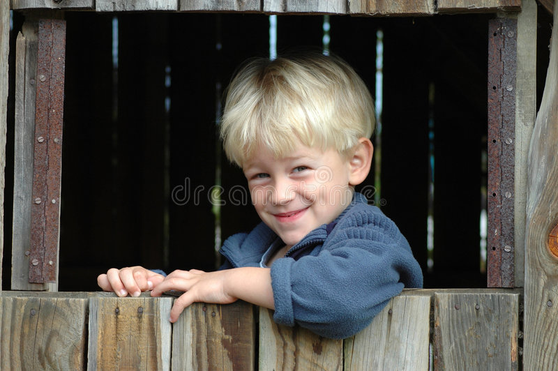 Blond child. A beautiful clever blond caucasian white boy child head portrait with happy smiling and smart expression in his handsome face looking out of the stock image
