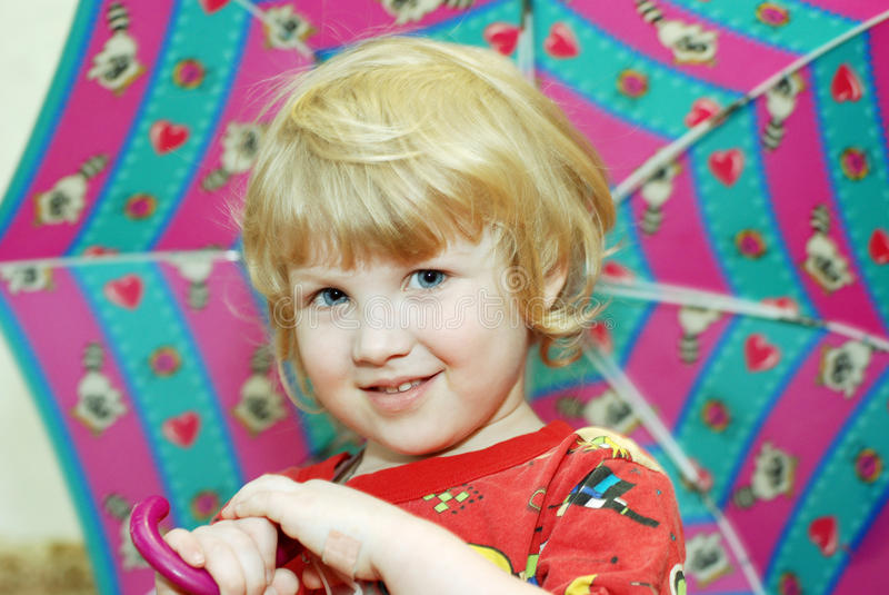 Blond child with umbrella stock image