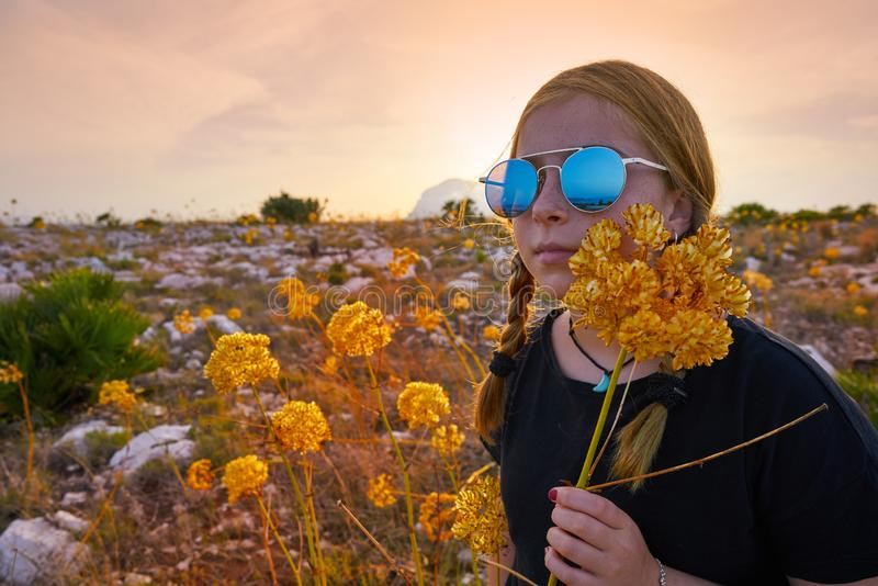 Blond country girl with sunglasses. And flowers at sunset outdoor mountain royalty free stock photography