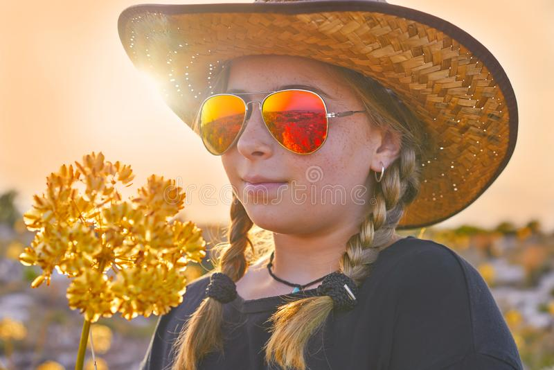 Blond country girl with sunglasses. And flowers at sunset outdoor mountain stock image