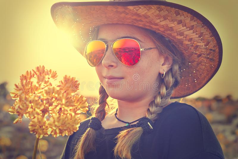 Blond country girl with sunglasses. And flowers at sunset outdoor mountain stock photos