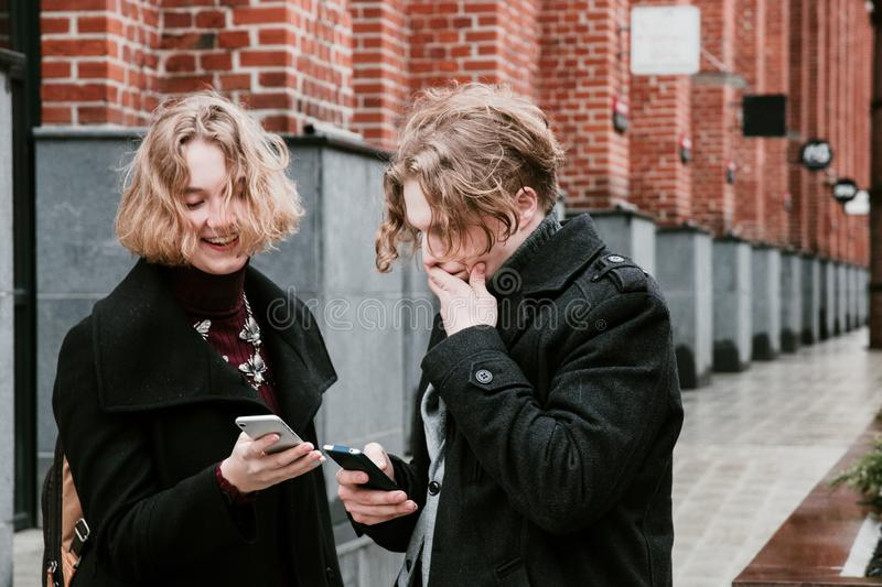 Blond curly-haired guy and the same girl are looking for information in mobile devices royalty free stock image
