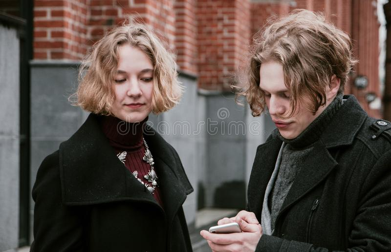 Blond curly-haired guy and the same girl are looking for information in mobile devices royalty free stock photography