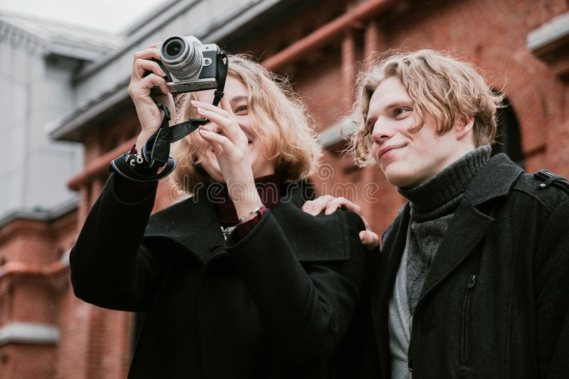 Blond curly-haired guy and the same girl take pictures of themselves and take pictures around stock images